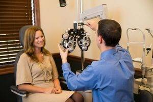 Dr. Hite giving a woman an eye exam at North Range Eye Care